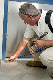 Pest management professional performing a crack and crevice treatment